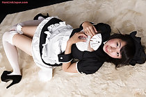 Lying on her back hands raised to her chest knees pressed together wearing maid uniform in stockings and high heels