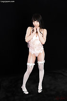 Wearing white lingerie wearing stockings in high heels hands clasped together under her chin